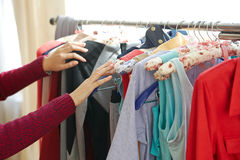 Weibliche Hände, die in der Kleidung durchstöbern Lizenzfreies Stockfoto