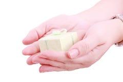 Weibliche Hände, die ein Geschenk geben. Stockbild