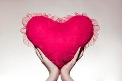 Weibliche Hände, die ein rosa oder rotes Plüschherz halten Zwei verklemmte Innere Lizenzfreie Stockbilder