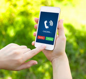 Weibliche Hände, die ein weißes Telefon mit Klingelnrohr auf dem scre halten lizenzfreie stockbilder