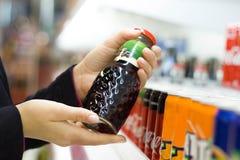 Weibliche Hände, die eine Flasche Saft im Supermarkt halten stockbilder