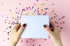Weibliche Hände, die eine Geschenkbox auf rosa Hintergrund, Draufsicht halten stockfoto