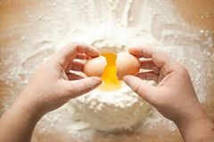 Weibliche Hände, die eine Hühnerei in Mehl brechen stockfotos