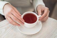 Weibliche Hände, die eine weiße Tasse Tee Draufsicht auf dem Tisch stehend halten Stockfotos