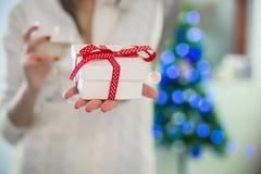 Weibliche Hände, die einen Präsentkarton, Porträt der jungen lächelnden Frau in verziertem Wohnzimmer mit Geschenken und Weihnach Lizenzfreies Stockfoto