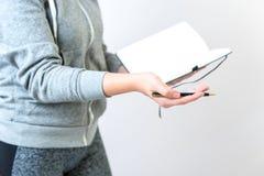 Weibliche Hände, die einen Stift und ein Notizbuch halten gestikulieren lizenzfreies stockbild