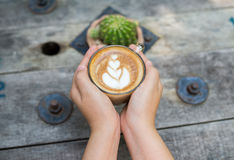 Weibliche Hände, die einen Tasse Kaffee über Holztisch, Draufsicht halten Lizenzfreies Stockfoto