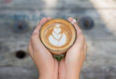 Weibliche Hände, die einen Tasse Kaffee über Holztisch, Draufsicht halten Lizenzfreie Stockbilder