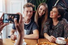 Weibliche Hände, die Foto der lächelnden Gruppe Freunde trinken Tee in einem gemütlichen Kaffeehaus mit Smartphone machen Stockfoto