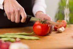 Weibliche Hände, die frische Tomate hacken Lizenzfreie Stockfotos