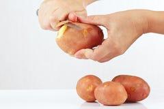 Weibliche Hände, die frischer Kartoffel mit einem Messer abziehen lizenzfreie stockbilder