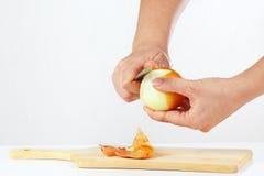 Weibliche Hände, die frischer Zwiebel mit einem Messer abziehen lizenzfreie stockfotografie