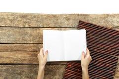 Weibliche Hände, die geöffnetes Buch halten Stockfotografie
