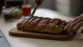 Weibliche Hände, die gebackene Torte auf hölzerner Platte schneiden stock video