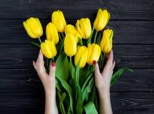 Weibliche Hände, die gelbe Tulpen auf schwarzem Weinleseholztisch halten Flache Lage, Draufsicht Stockbild