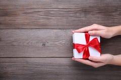 Weibliche Hände, die Geschenkbox auf grauem Holztisch halten lizenzfreies stockbild