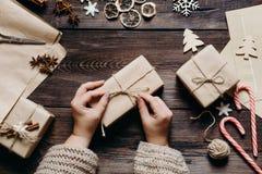 Weibliche Hände, die Geschenke einwickeln und verzieren lizenzfreie stockbilder