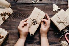 Weibliche Hände, die Geschenke einwickeln und verzieren stockfoto