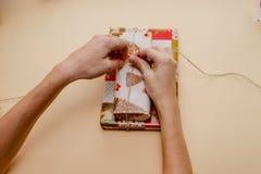 Weibliche Hände, die Geschenke halten und Geschenke verpacken stockfotografie