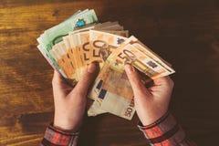 Weibliche Hände, die große Menge Eurowährungsbargeld banknot zählen Lizenzfreies Stockbild