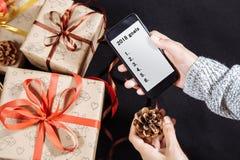 Weibliche Hände, die Handy auf dunklem Hintergrund mit Weihnachtsgeschenken halten Weihnachts- und guten Rutsch ins Neue Jahr-Zus lizenzfreies stockfoto
