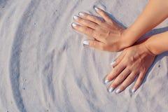 Weibliche Hände, die im Sand spielen Stockbilder