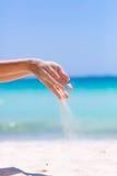 Weibliche Hände, die im Sand spielen Lizenzfreie Stockfotos