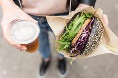 Weibliche Hände, die köstlichen organischen Salmon Vegetarian Burger und Homebrewed IPA-Bier halten stockfotografie