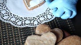 Weibliche Hände, die Lebkuchenstrumpf mit Puderzucker unter Verwendung der selbst gemachten Gebäcktasche verzieren stock video