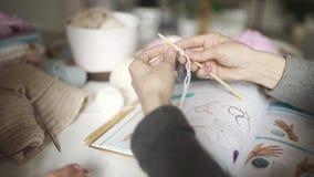 Weibliche Hände, die lernen, unter Verwendung des strickenden Musters zu stricken Frauenfreizeit stock video