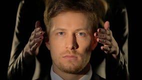 Weibliche Hände, die männliche Augen, Energie über Männern, Konzept der blinden Gerechtigkeitsnahaufnahme schließen stock video