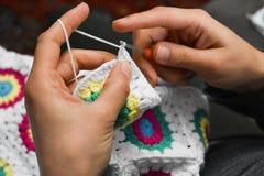 Weibliche Hände, die mit bunter Wolle stricken stockbilder
