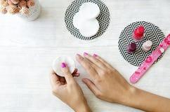 Weibliche Hände, die Nagellack von den Nägeln auf Holztisch entfernen Stockbild