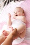 Weibliche Hände, die nette Babyfüße halten Lizenzfreie Stockfotografie