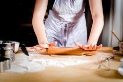 Weibliche Hände, die oben Teig auf Küchentisch, Abschluss bereitstellen Lizenzfreie Stockfotos
