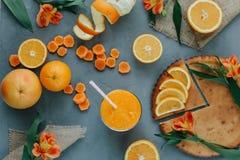 Weibliche Hände, die orange Smoothie verziert mit Alstroemeria mit orange Torte halten stockfotos