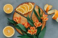Weibliche Hände, die orange Smoothie verziert mit Alstroemeria mit orange Torte halten lizenzfreies stockbild