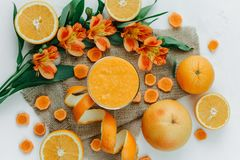 Weibliche Hände, die orange Smoothie verziert mit Alstroemeria mit orange Torte halten lizenzfreies stockfoto
