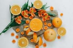 Weibliche Hände, die orange Smoothie verziert mit Alstroemeria mit orange Torte halten lizenzfreie stockfotos