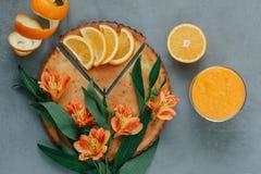 Weibliche Hände, die orange Smoothie verziert mit Alstroemeria mit orange Torte halten stockfotografie