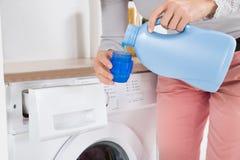 Weibliche Hände, die Reinigungsmittel in der Flaschenkapsel gießen stockfoto
