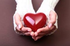 Weibliche Hände, die rotes Herz, auf Goldhintergrund geben Stockbild