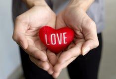 Weibliche Hände, die rotes Herz geben Stockfotografie