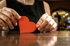 Weibliche Hände, die rotes Papierherz und copyspace halten Lizenzfreie Stockfotos