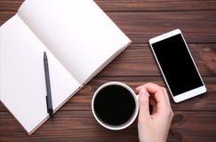Weibliche Hände, die Tasse Kaffee und Smartphone auf braunem hölzernem Hintergrund halten stockfotografie