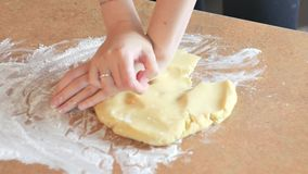 Weibliche Hände, die Teig im Mehl auf Tabelle kneten stock footage