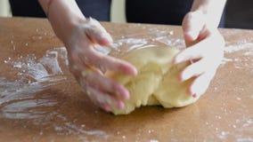 Weibliche Hände, die Teig im Mehl auf Tabelle kneten stock video