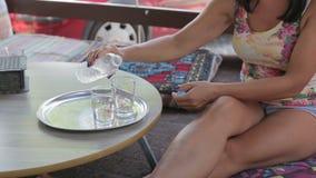 Weibliche Hände, die Trinkwasser in ein Glas gießen stock video footage