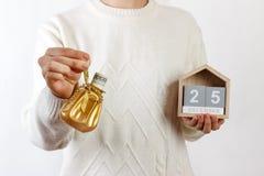 Weibliche Hände, die Weihnachtsgeschenkbox mit Dollar und Kalender, Weihnachten halten 25 Desember Hintergrund Feriengeschenk und Lizenzfreies Stockfoto