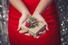 Weibliche Hände, die Weihnachtsgeschenkbox mit Niederlassung des Tannenbaums, glänzender Weihnachtshintergrund halten Stockbilder